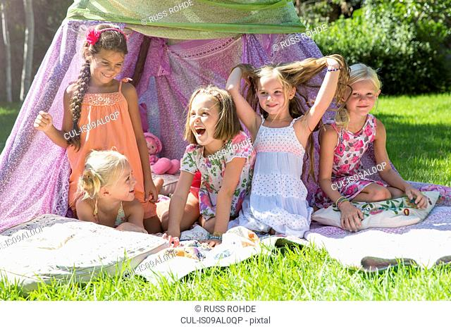 Five girls playing in garden teepee