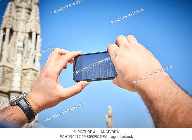 05 April 2019, Italy, Mailand: A tourist at the Milan Cathedral takes a picture with his mobile phone of the tops of the roof