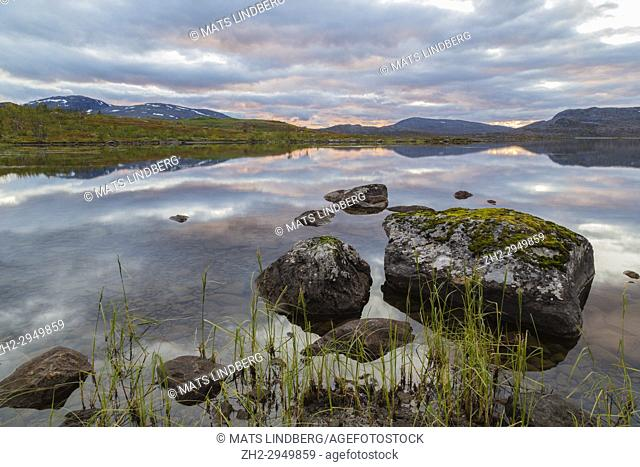 View over a small lake in autumn with color full trees and busches, big rocks in the foreground, sunset making nice colors on the sky and cllouds, Kiruna