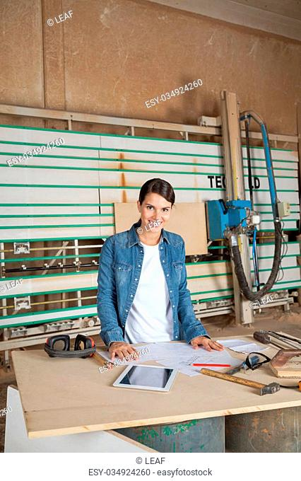 Portrait of confident female carpenter standing at table against vertical panel saw