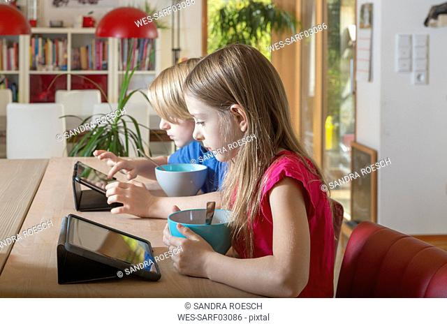 Boy and girl using tablets at breakfast table