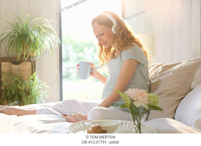 Pregnant woman drinking coffee and listening to music with headphones and digital tablet on bed