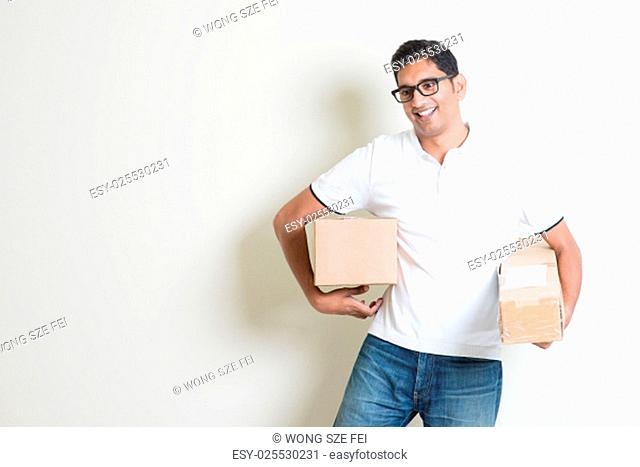 Courier delivery service concept. Happy Indian man holding brown boxes, standing on plain background with shadow. Asian handsome guy model