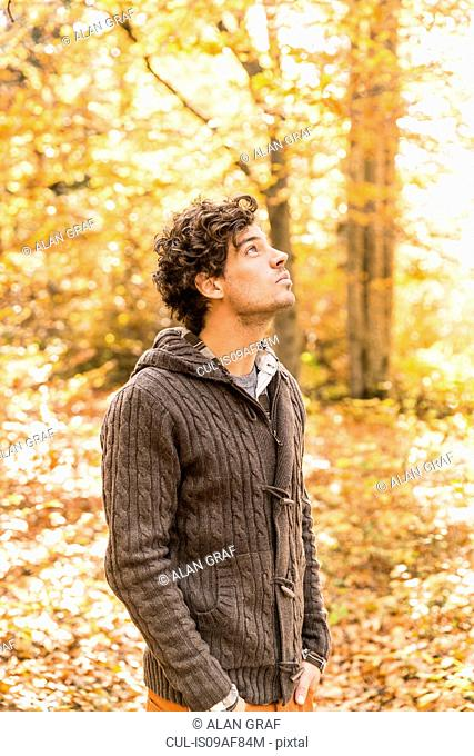 Portrait of man wearing cardigan in forest looking up
