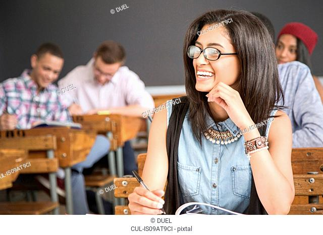 Female student, sitting at desk in classroom, smiling