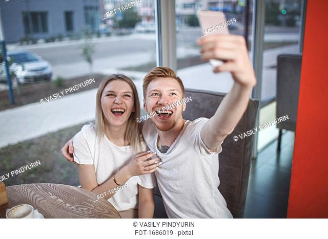 High angle view of happy young couple taking selfie with mobile phone while sitting at restaurant
