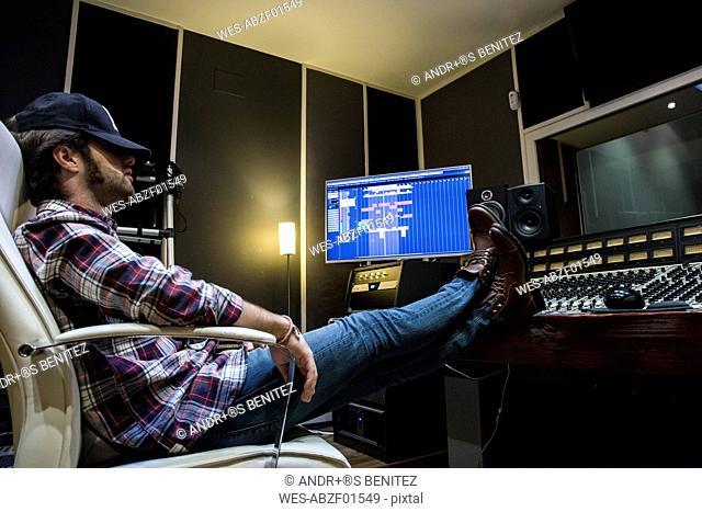 Man resting with his feet on the mixing board in a recording studio