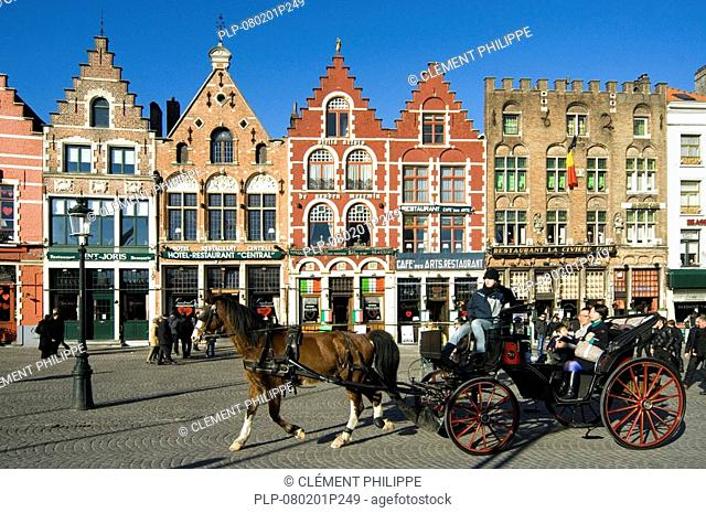 Colourful Façades of restaurants and coach with tourists at the Market place, Bruges, Belgium