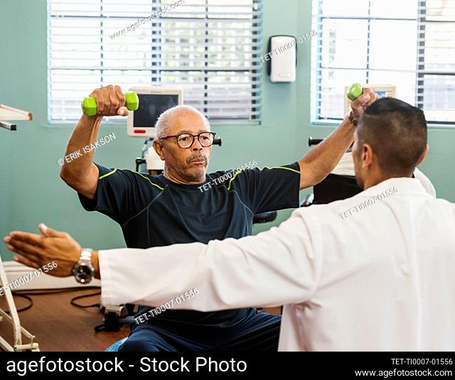 Senior man exercising with therapist during physical therapy