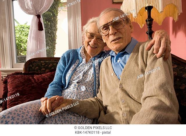 Affectionate senior couple sitting on sofa in living room