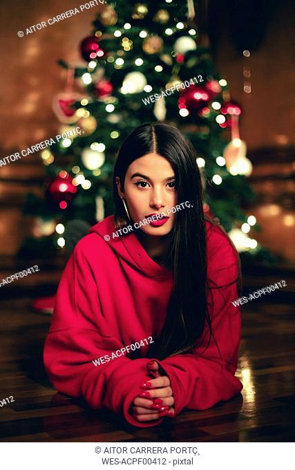 Portrait of teenage girl lying on the floor in front of Christmas tree