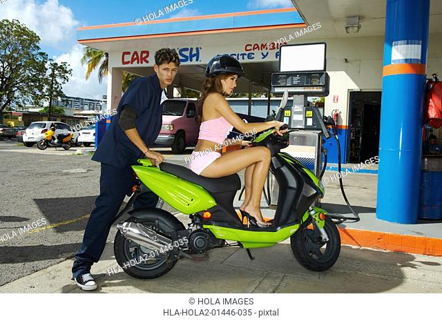 Gas station attendant getting onto womans scooter