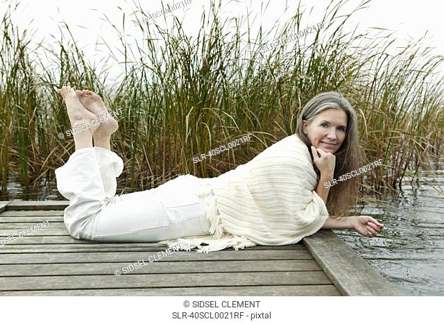 Older woman relaxing on wooden dock