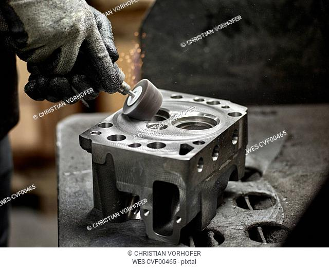 Worker in metalworking factory grinding cylinder head