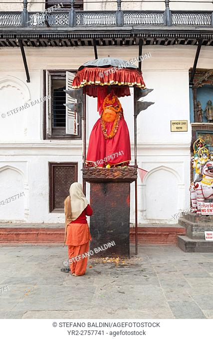 Woman worshiping at Hanuman statue, Durbar Square, Kathmandu, Nepal