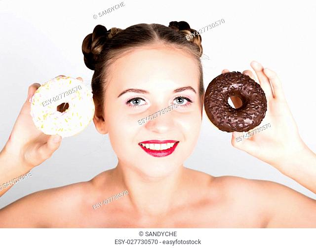girl in bright makeup eating a tasty donut with icing. Funny joyful woman with sweets, dessert. dieting concept. junk food