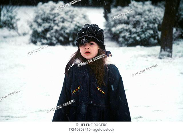 Child In Winter Coat In The Snow with a Woollen Hat