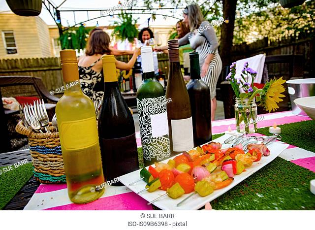 Group of people at garden party, holding wine glasses, making a toast, focus on row of wine bottles in foreground
