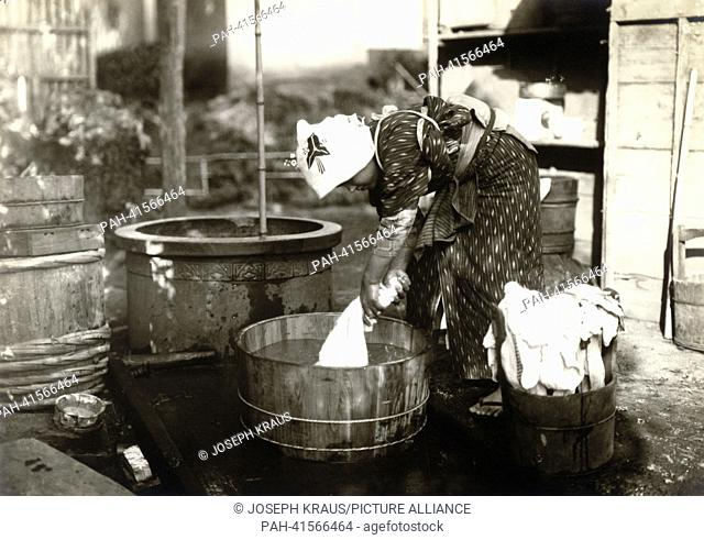 Farmers wife washing cloth in a tub Pictured in the early 1920th. - /Japan