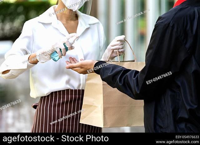 Waitress spraying alocohol on hand of deliverly man before give bakery grocery bag for cleaning and hygiene as new normal for Food deliverly service while...