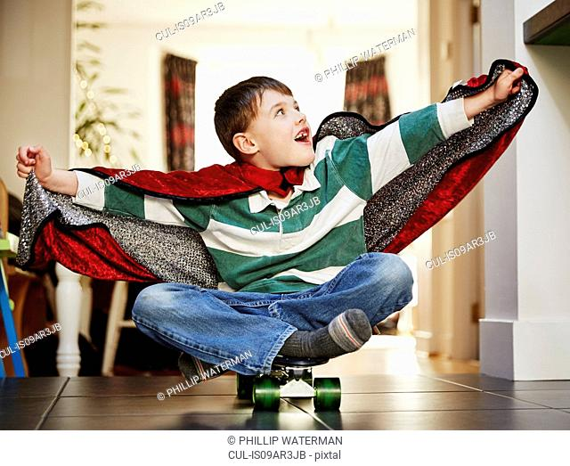 Young boy sitting on skateboard wearing cape