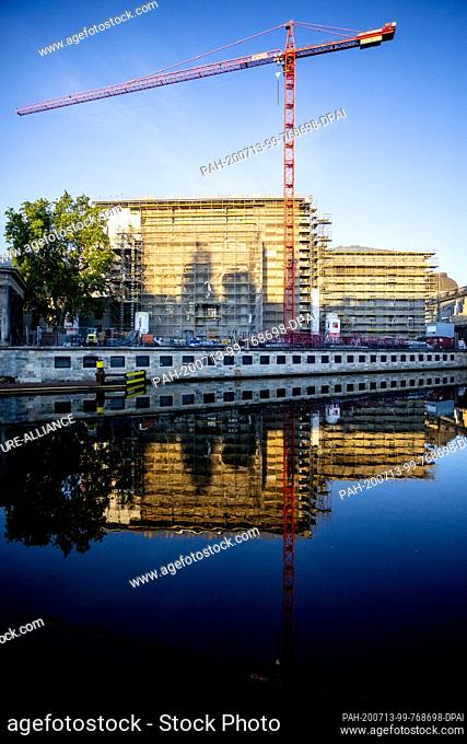 13 July 2020, Berlin: The Pergamonmuseum, which is currently under construction, is reflected in the light of the rising sun in the Spree
