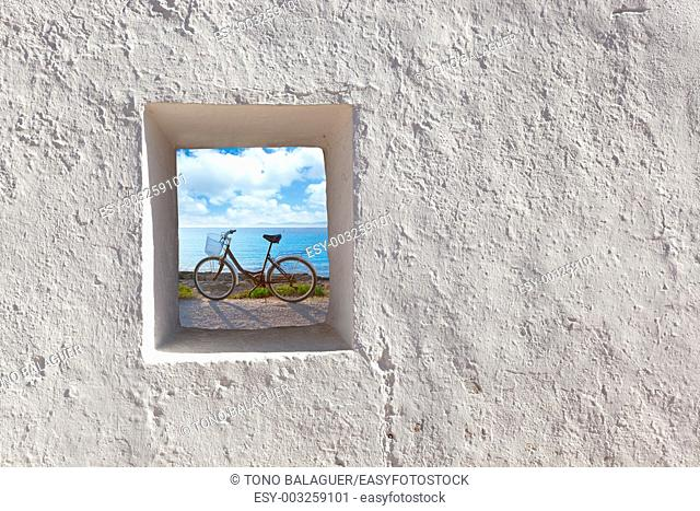 Balearic islands beach and bicycle view through whitewashed house window