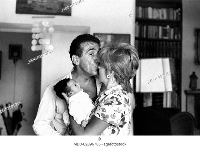 Italian actor and dubber Arnoldo Foà kissing his Italian wife, Ludovica Volpe. She's clasping in her arms their daughter Orsetta Foà. Rome, 1970s