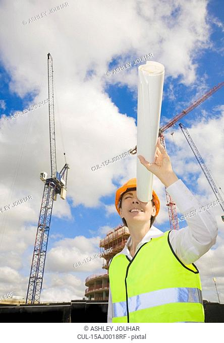 Woman Looking down tube at building site