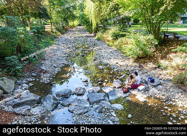 09 August 2020, Baden-Wuerttemberg, Bad Krozingen: Wiktoria (l) and Gabriel are sitting in the almost dry riverbed of the Neumagen river