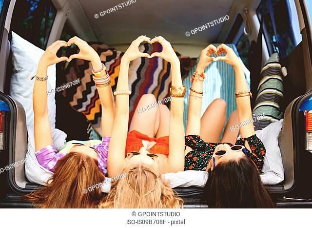 Three young women lying on backs in car boot making heart sign