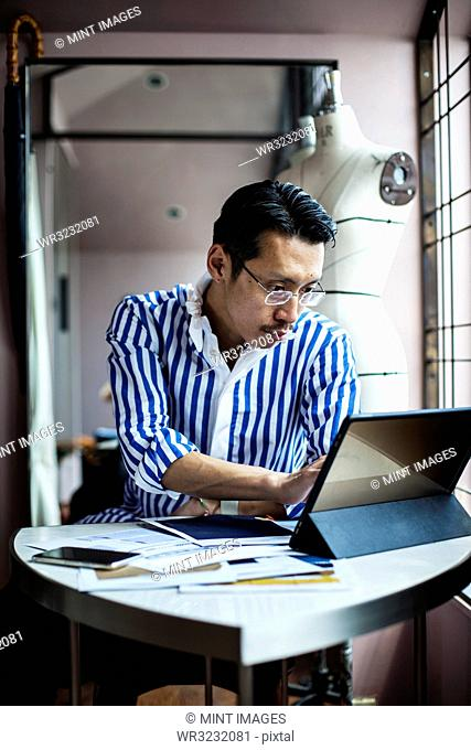 Japanese male fashion designer working in his studio, sitting at table, looking at digital tablet