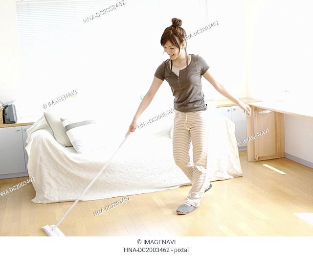 Woman Sweeping Floor in Living Room