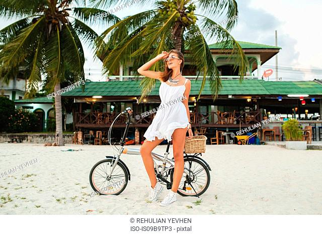 Young woman with bicycle looking away on sandy beach, Krabi, Thailand