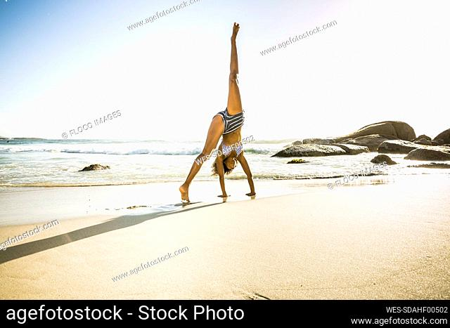 Young woman doing a cartwheel on the beach
