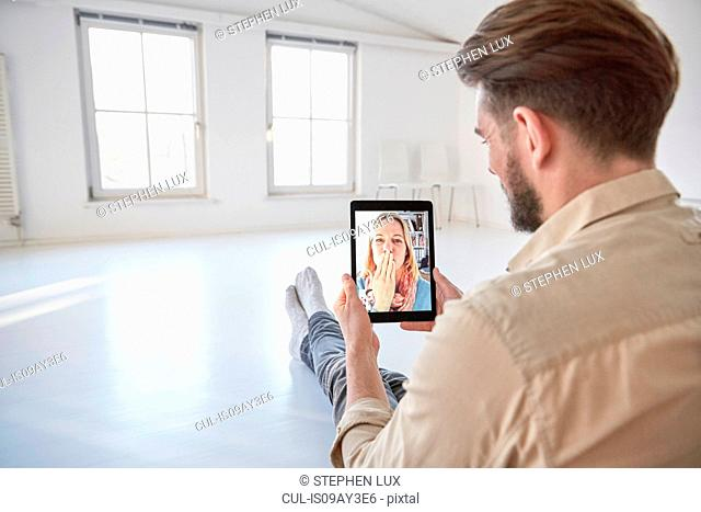 Girlfriend on digital tablet video call blowing a kiss to young man sitting on floor