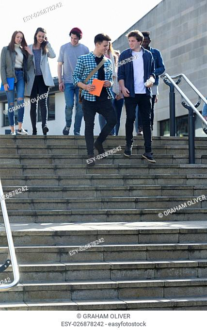 A group of students laugh and smile as they leave one of their lectures. They are walking down some steps carrying their books, bags and digital tablets