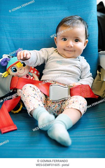 Happy baby girl sitting on a plane seat with a doll and the seat belt fastened
