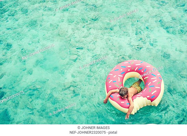 Boy swimming on inflatable ring