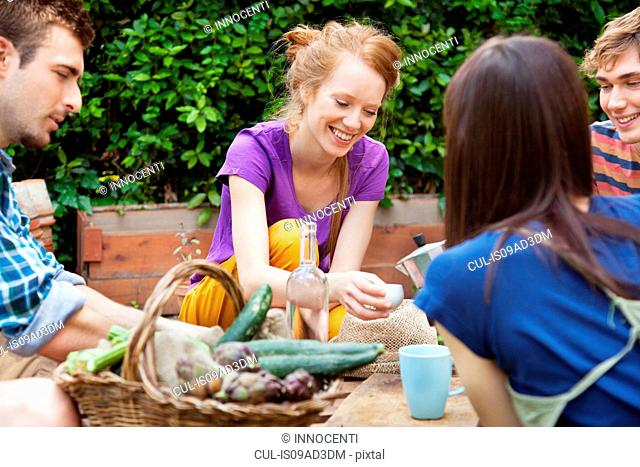 Friends sitting in garden with basket of fresh vegetables