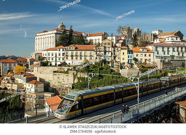 Metro train crosses Luis I Bridge in Porto, Portugal. Ribeira in the distance