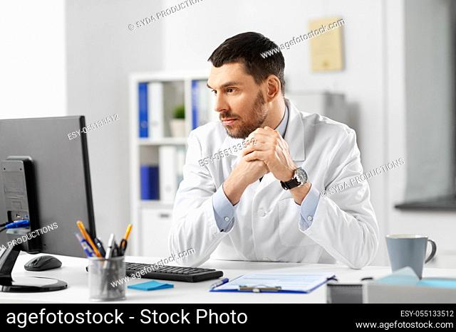 doctor with clipboard and computer at hospital