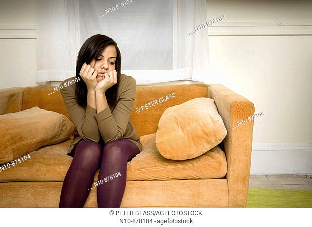 Young woman sitting on her sofa