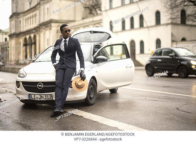 Man leaning against car, Munich, Germany