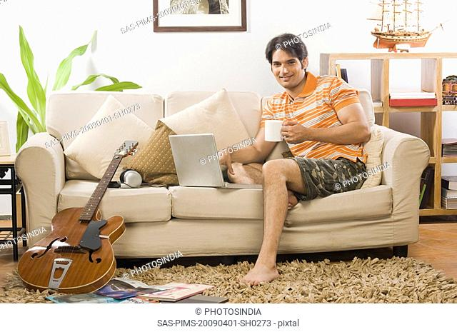 Young man holding a coffee mug in the living room