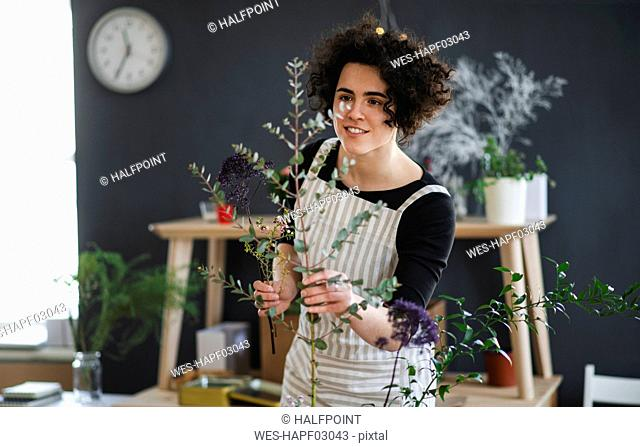 Smiling young woman arranging flowers in a small shop