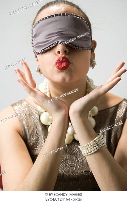 Young woman with hand on chin, wearing eye mask