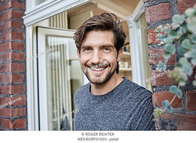 Portrait of smiling man at house entrance