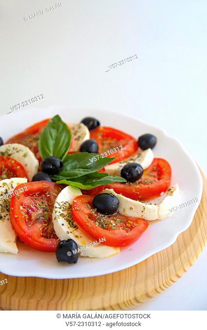 Mediterranean salad: sliced tomato, cottage cheese, black olives, basil and olive oil