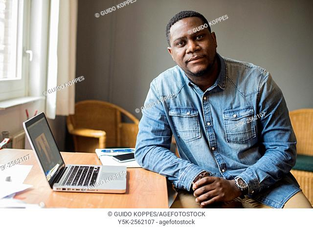 Tilburg, Netherlands. Portrait of a man with African ethnicity working behind his notebook computer